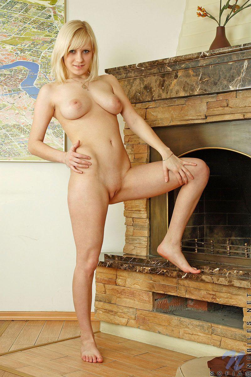 Молодая модель со свелыми волосами Sofia Nubiles с гигантскими сисяндрами показывает киску у камина