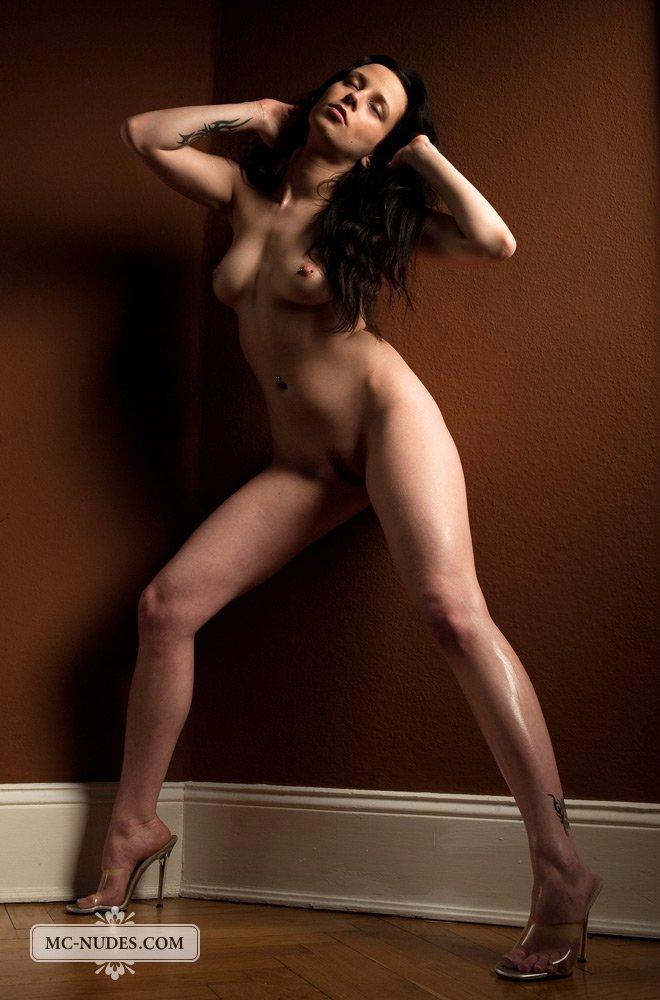 Возбуждающая модель с темными волосами Damjana Estrella выглядит изумительно, когда опирается на стену
